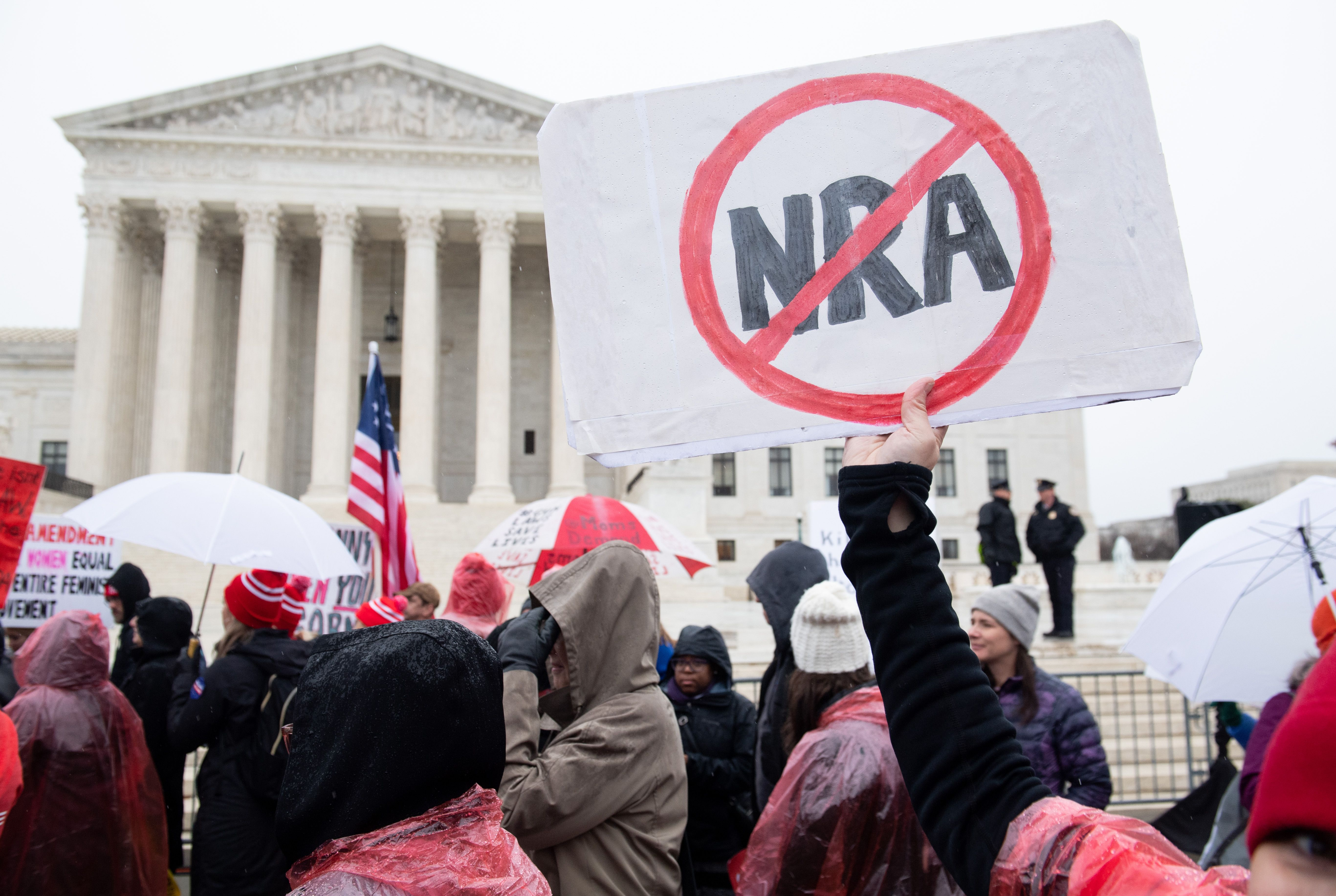Protesters outside the Supreme Court building holds up a sign that has the red-circled letters NRA on it with a line through them.