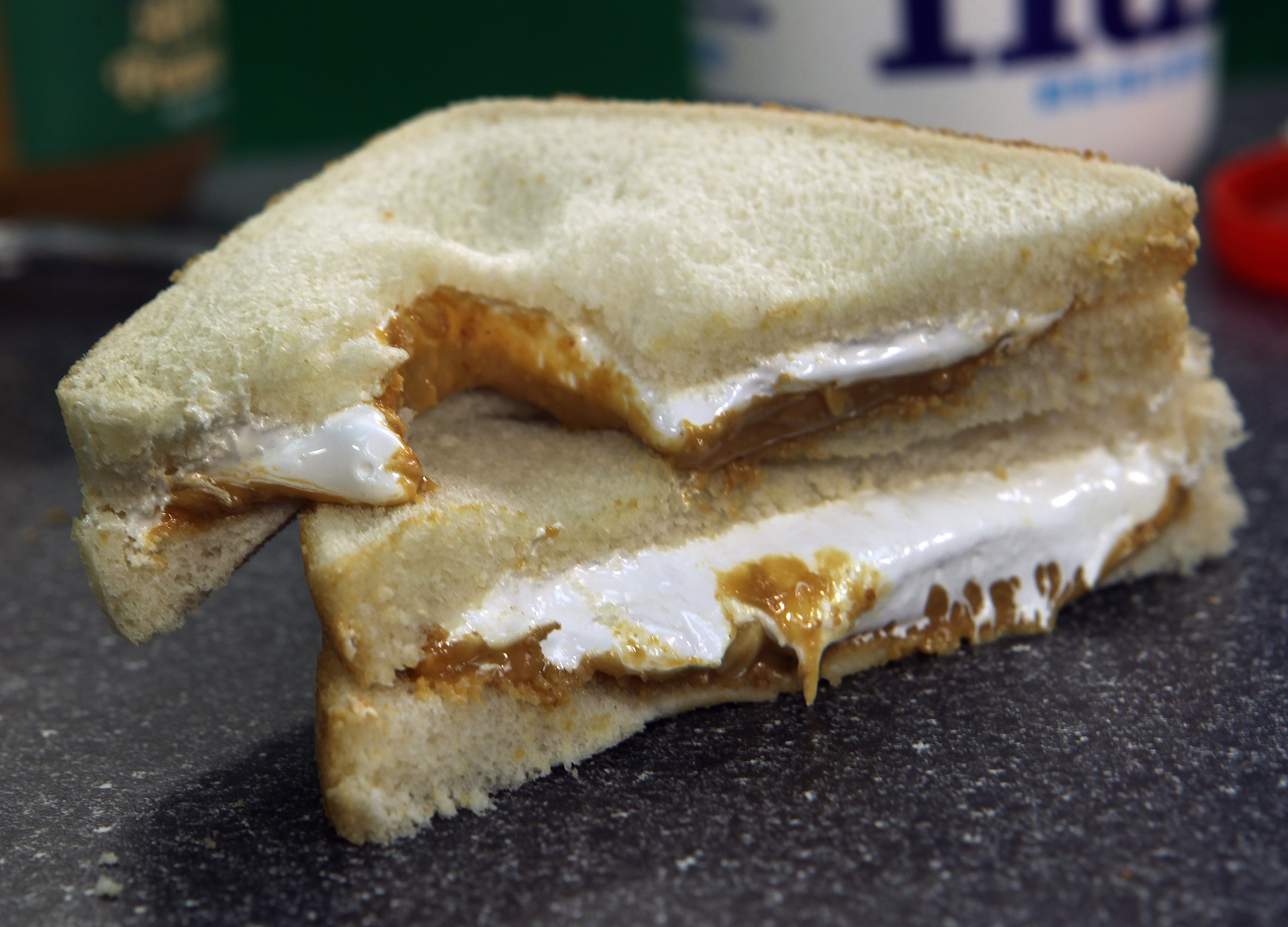 A sandwich on white bread is cut on the diagonal, with one half stacked on the other. It's filled with peanut butter and marshmallow Fluff.
