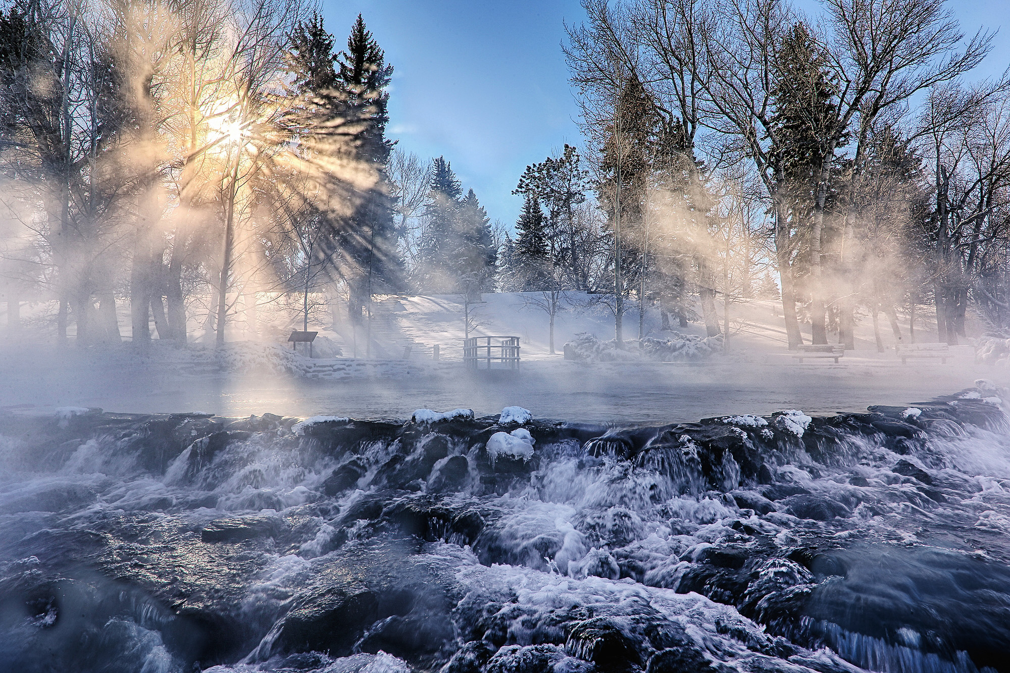 Steam rises from water in sub-zero temperatures as the sun shines through the trees at Giant Springs State Park in Montana.