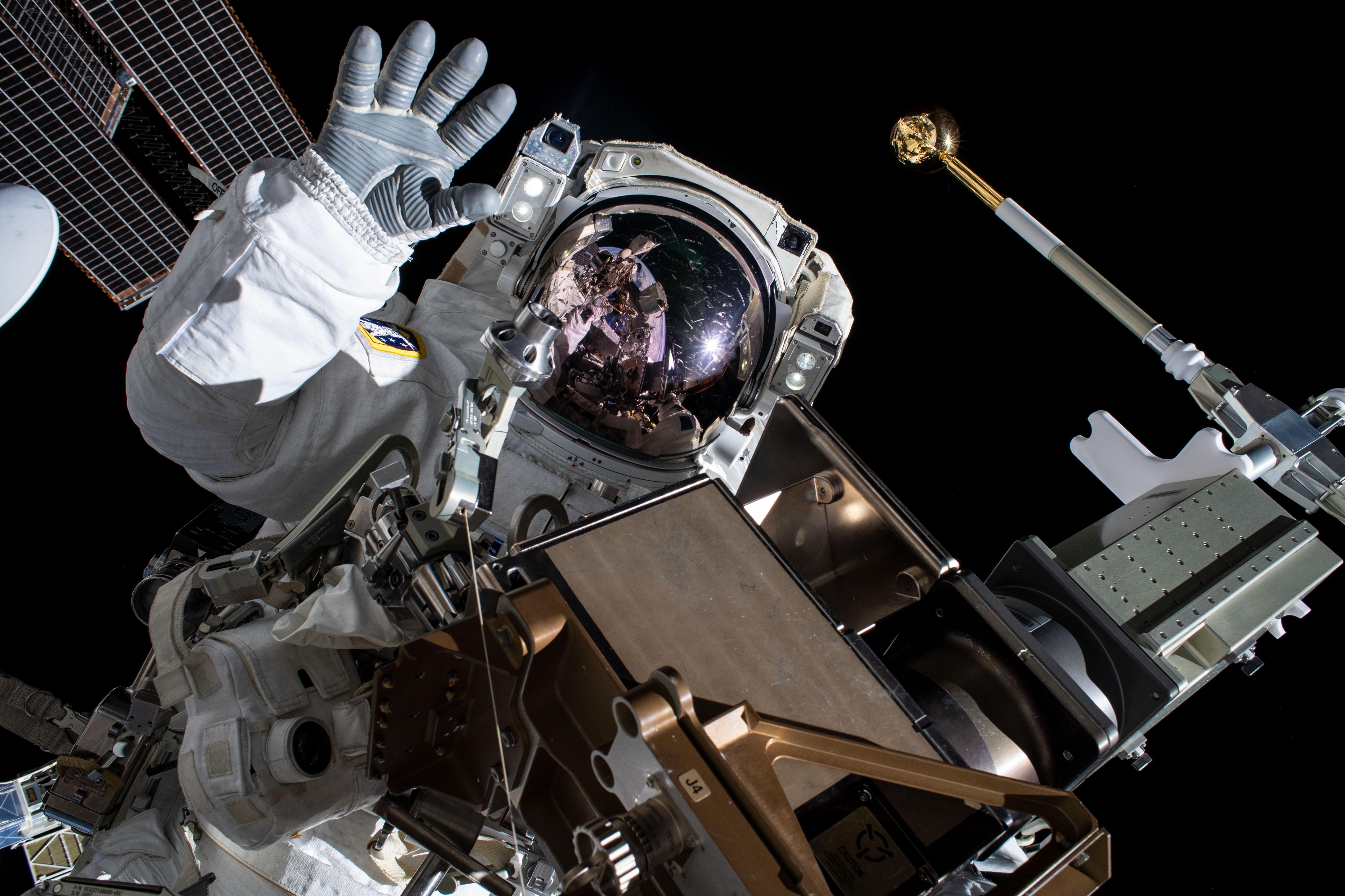 A Nasa astronaut waves hello toward a camera.