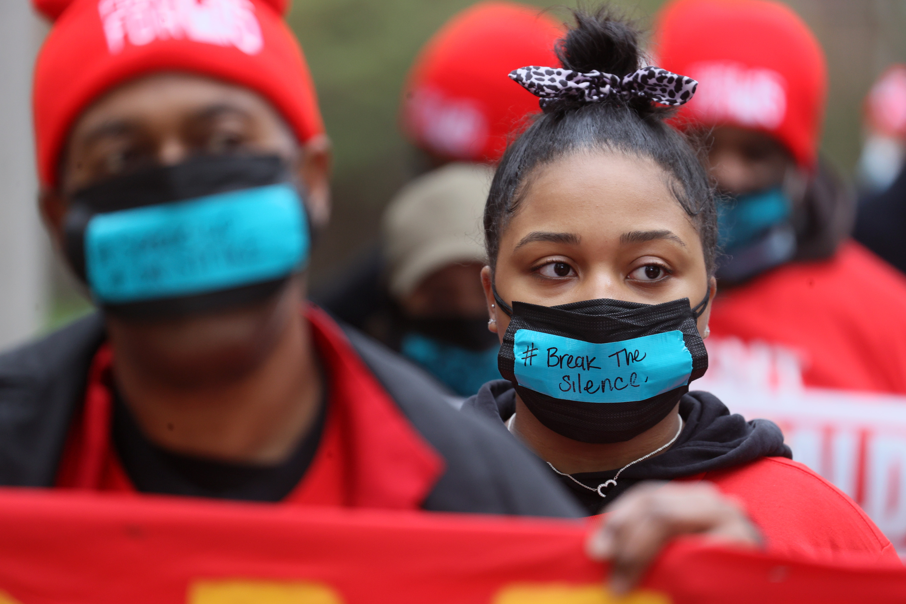 """A man and a woman, both wearing black facemasks with blue stickers on the front that say """"Break the Silence"""", carry a red protest sign together"""