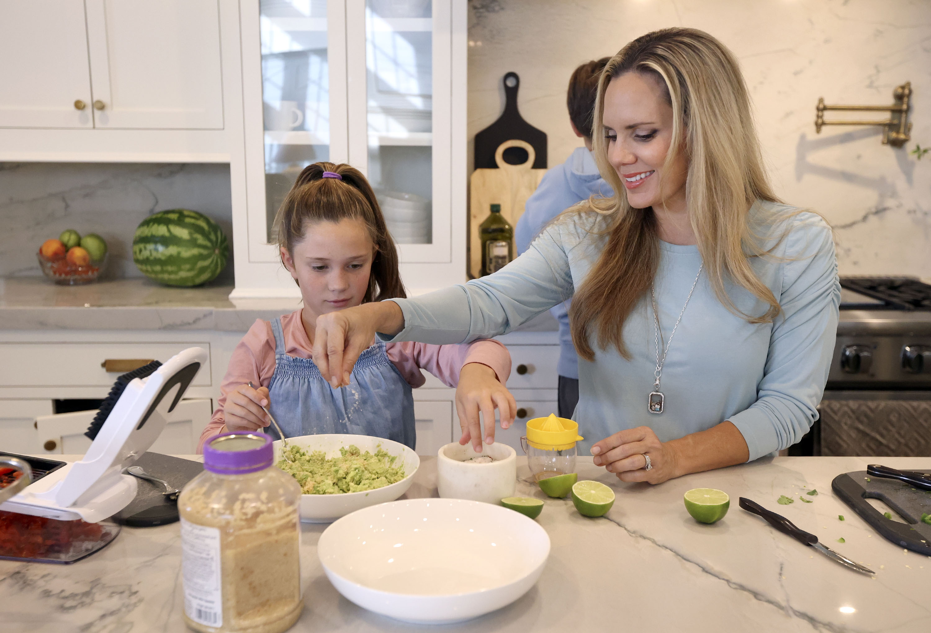 Grace Denney and her mother, Christy Denney, add salt to guacamole while making dinner for the rest of the family at their home in Highland on Wednesday, Oct. 13, 2021.