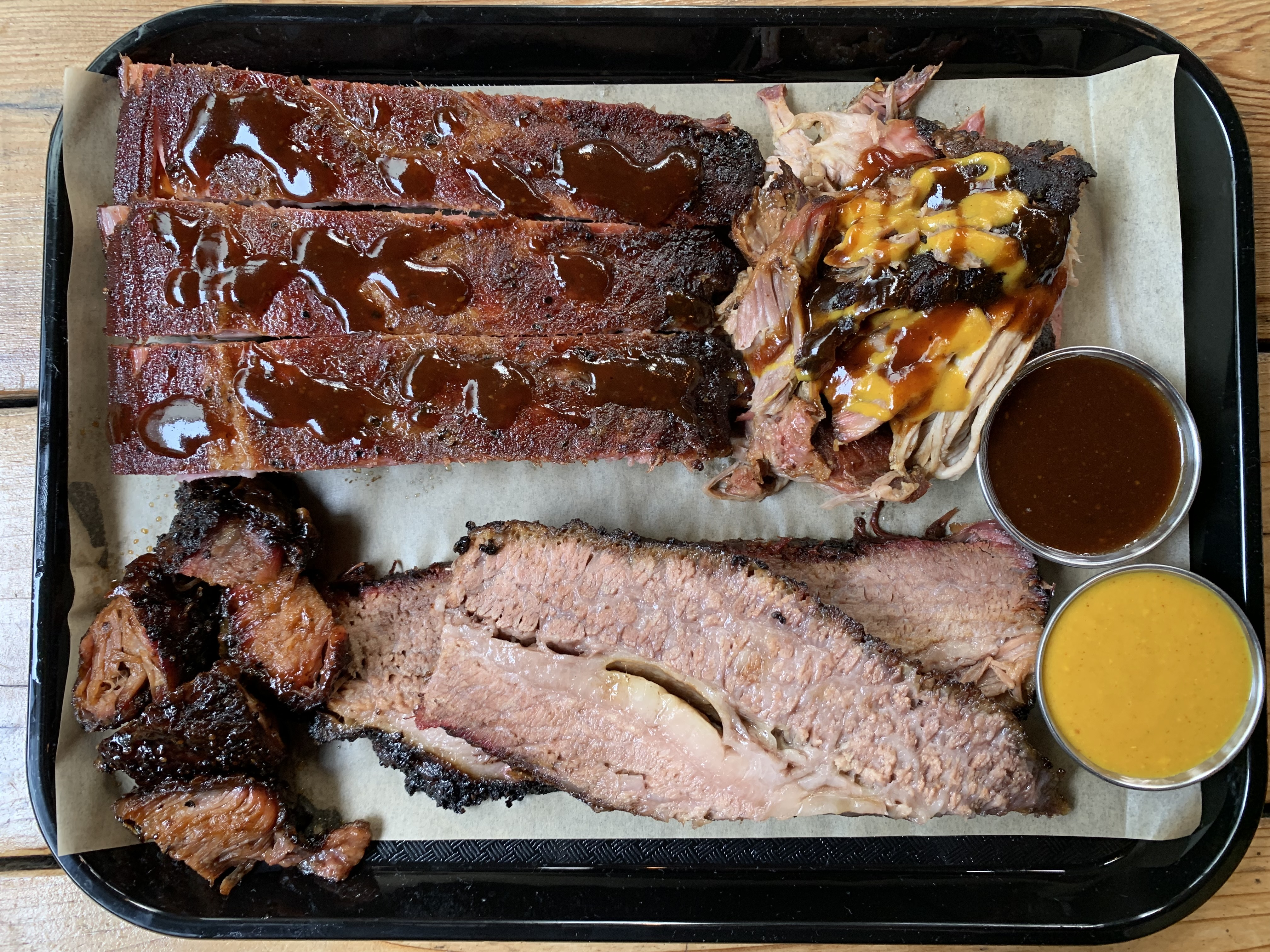 A platter of barbecue—clockwise featuring pork ribs, pulled pork, red and yellow barbecue sauces, slabs of brisket, and sauced burnt ends.