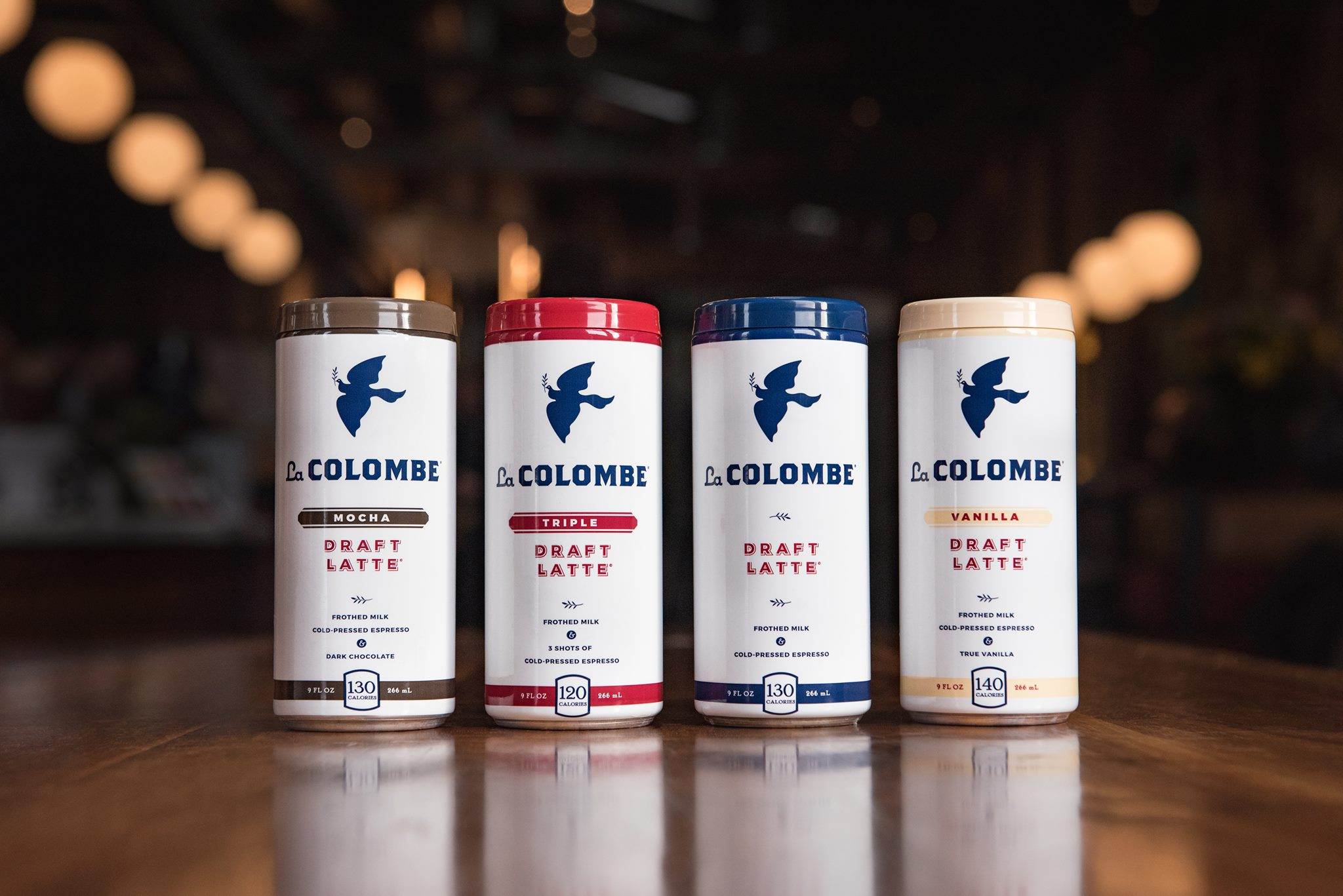 Four tall cans of coffee with white and colored trim details reading La Colombe.