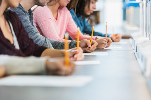 Several students sit at a gray table to take an exam using bright, yellow pencils. The classroom background is white.