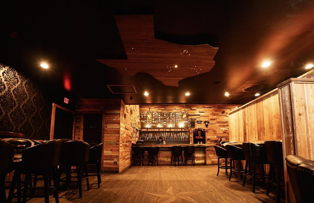 A bar with a lot of wood details and a beer tap system in the back.