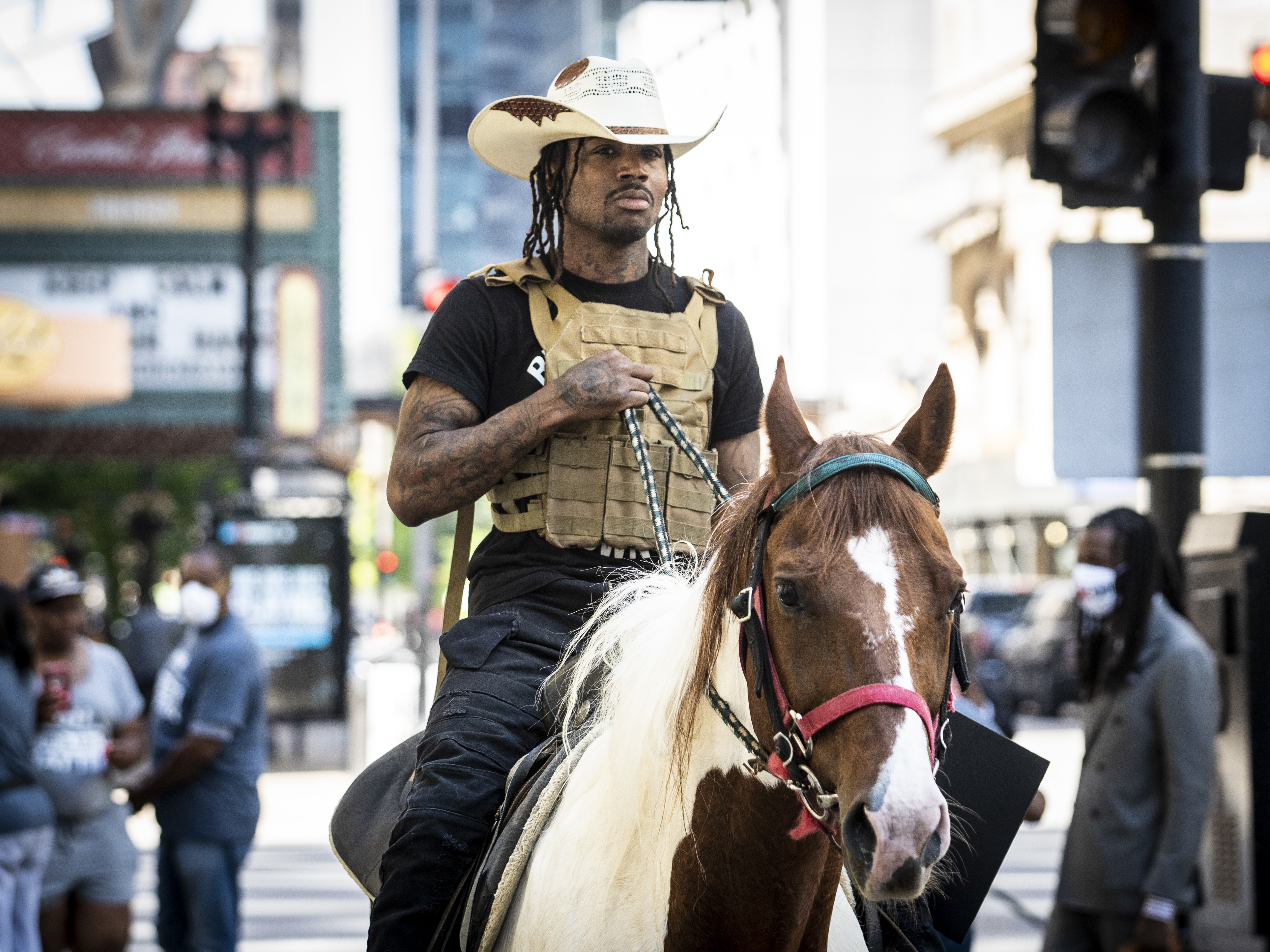 """Adam Hollingsworth, otherwise known as """"The Dread Head Cowboy,"""" rides his horse Prince in the Loop on June 16, 2020."""