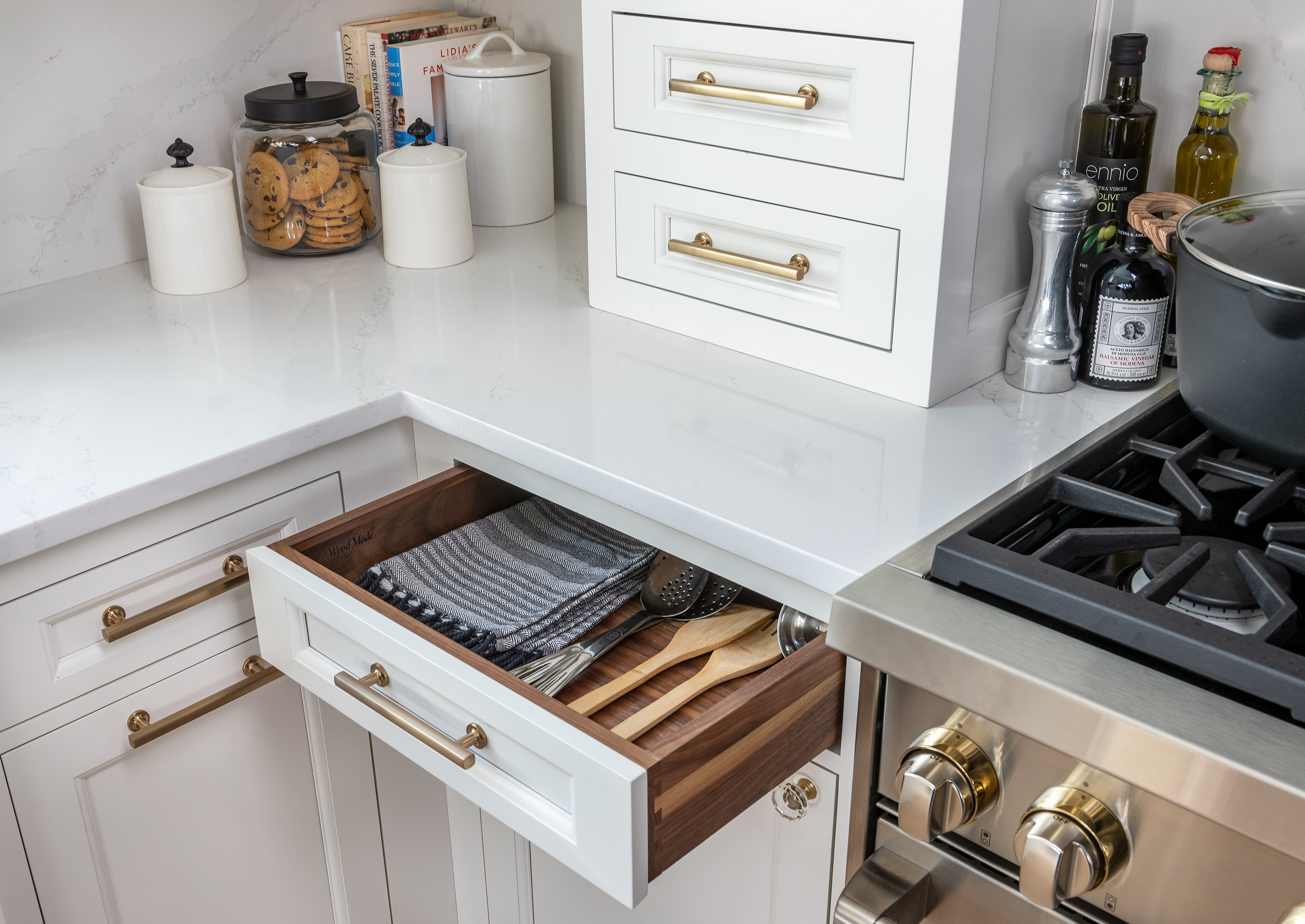 A close up of white kitchen cabinets with a drawer open.