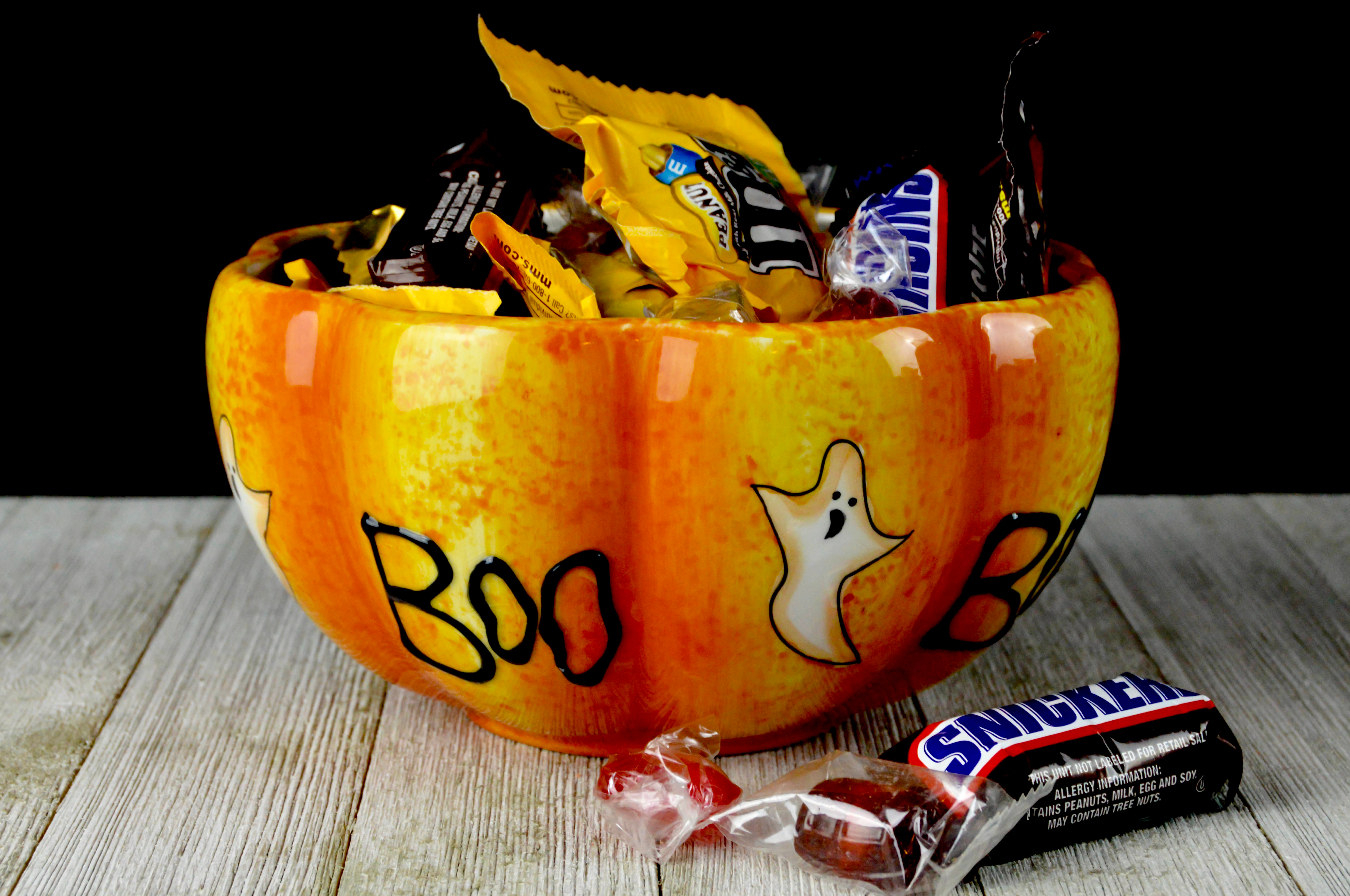 """An orange ceramic bowl, shaped like the bottom half of a pumpkin and painted with ghosts and the word """"boo,"""" overflows with name-brand candy like Snickers and peanut M&Ms."""