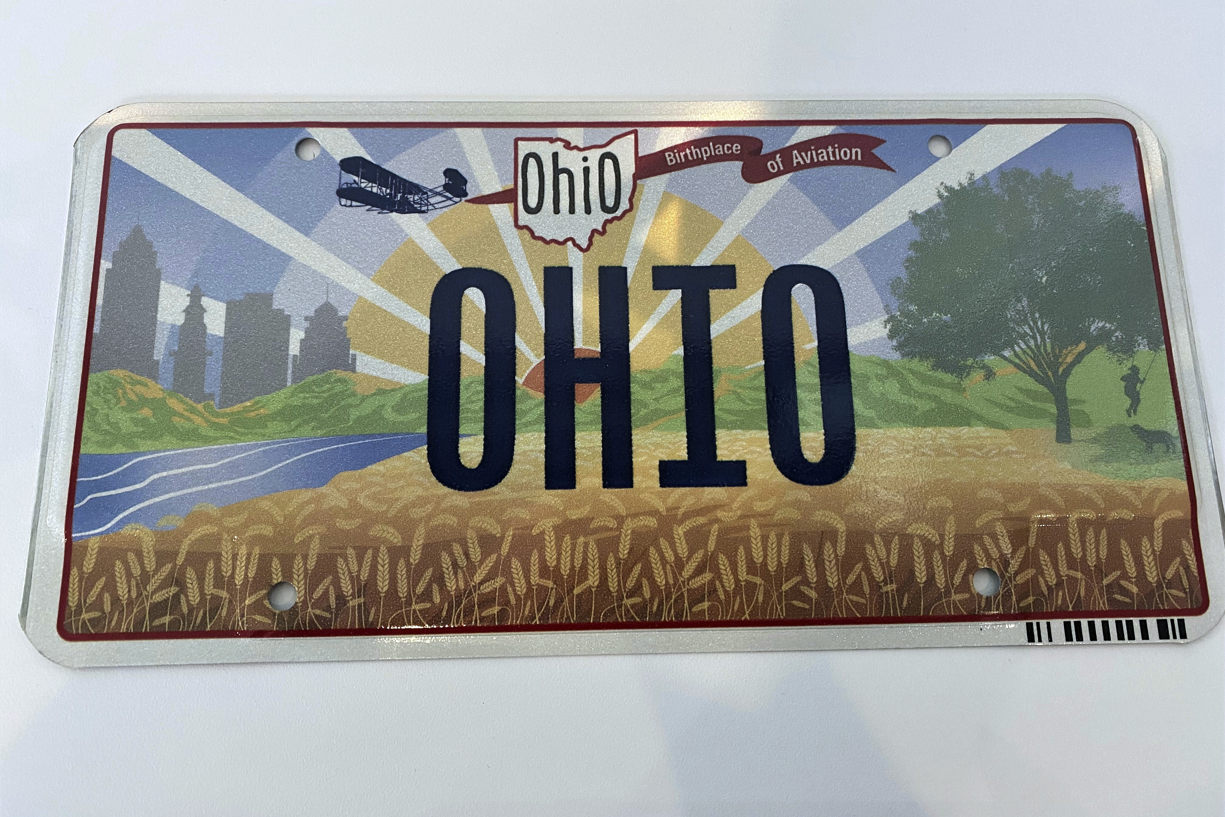 """Ohio's new """"Sunrise in Ohio"""" license plate failed to take off after officials realized that the illustration of a banner in flight was attached to the wrong end of the Wright Brothers' first plane. The new plate's banner reads """"Birthplace of Aviation."""" The banner should have been trailing behind the plane but was attached to the front."""