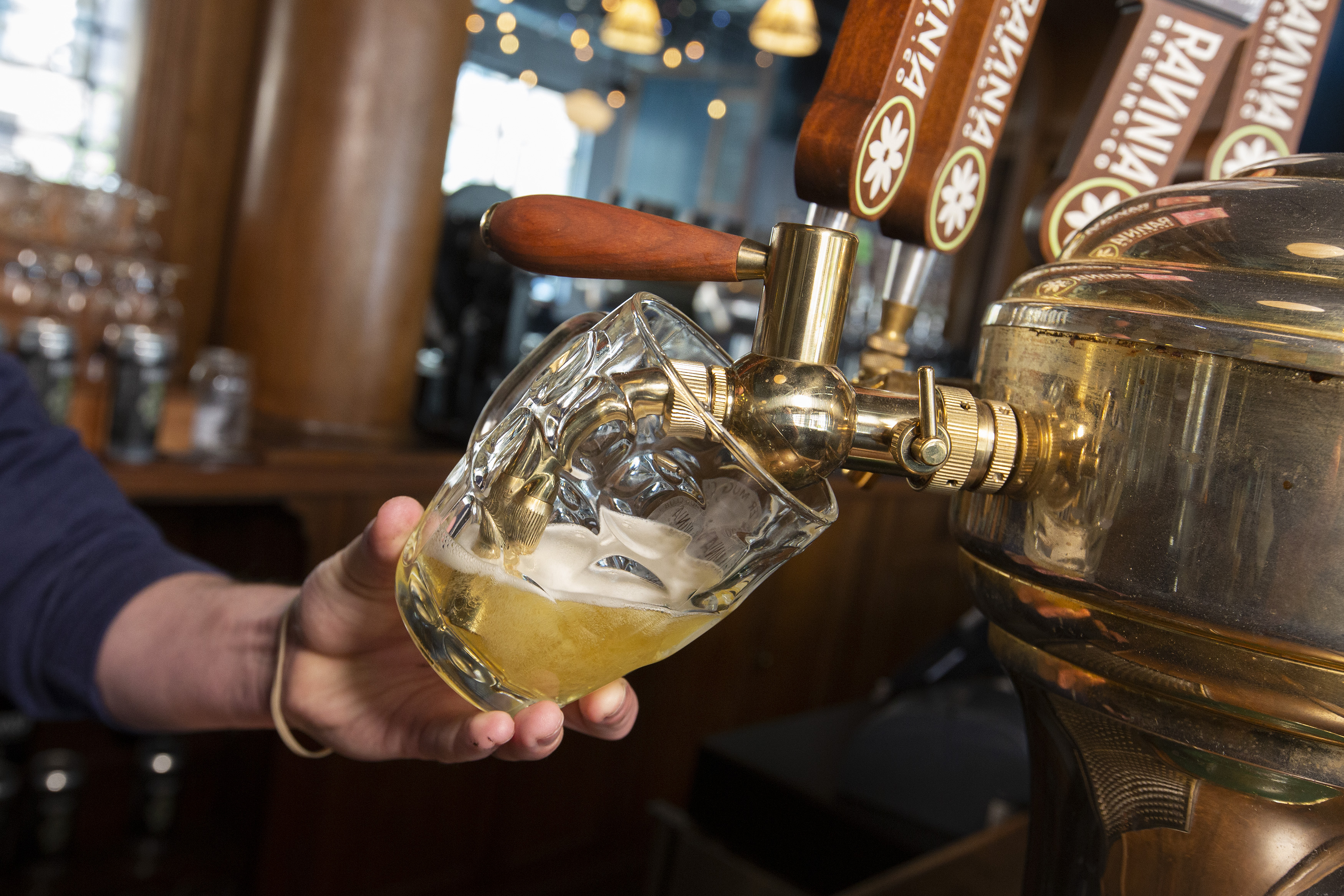 A person pours beer from a tap into a small glass.