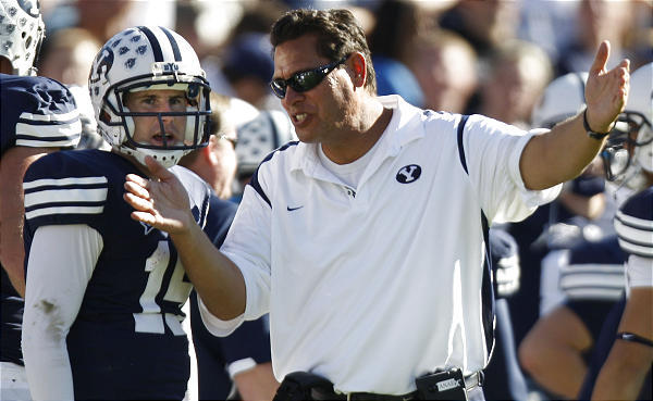 BYU offensive coordinator Robert Anae coaches up quarterback Max Hall on the sidelines.