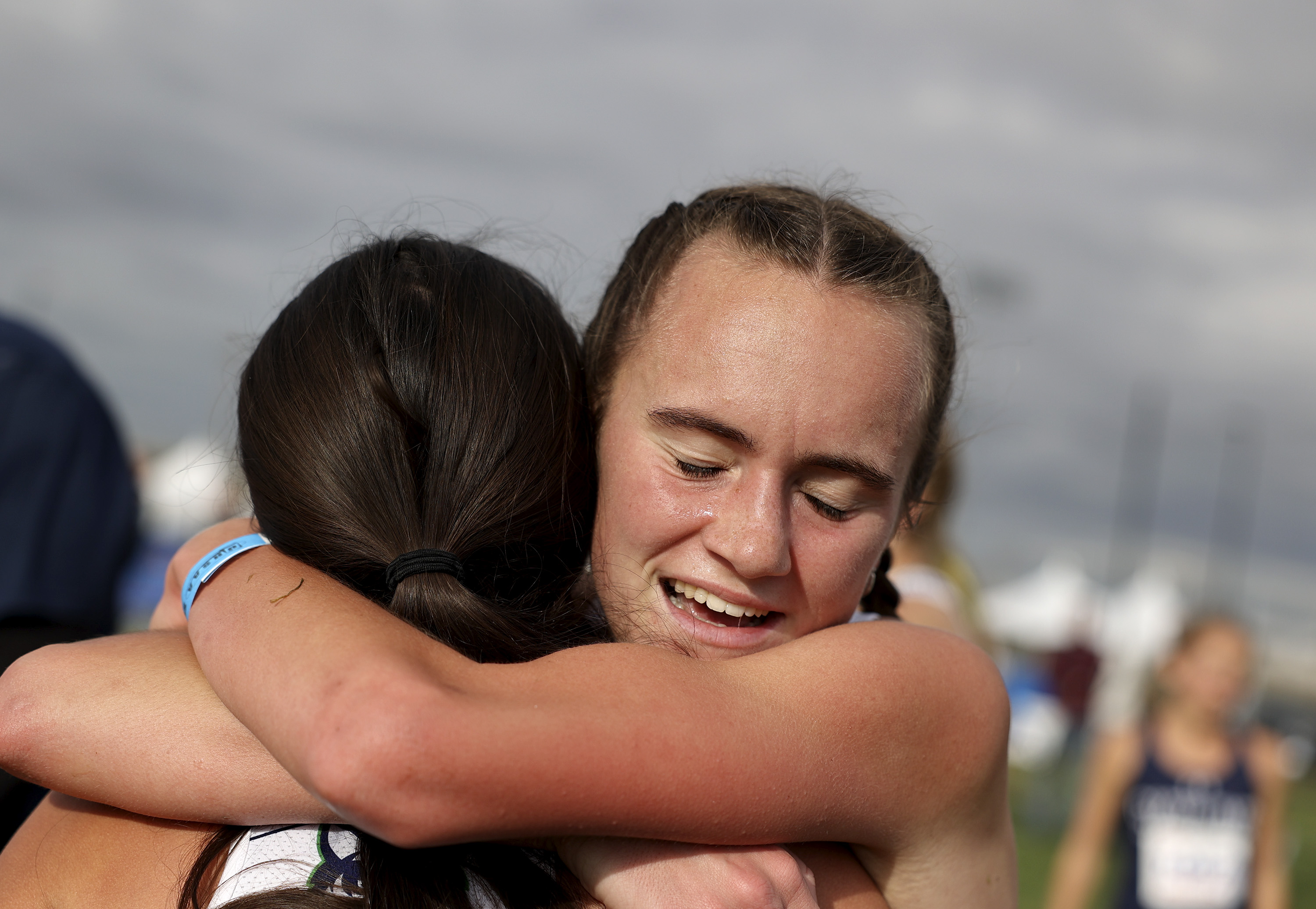 Raygan Peterson of Timpanogos High School is congratulated after finishing in first place in the 5A girls cross-country state championships.