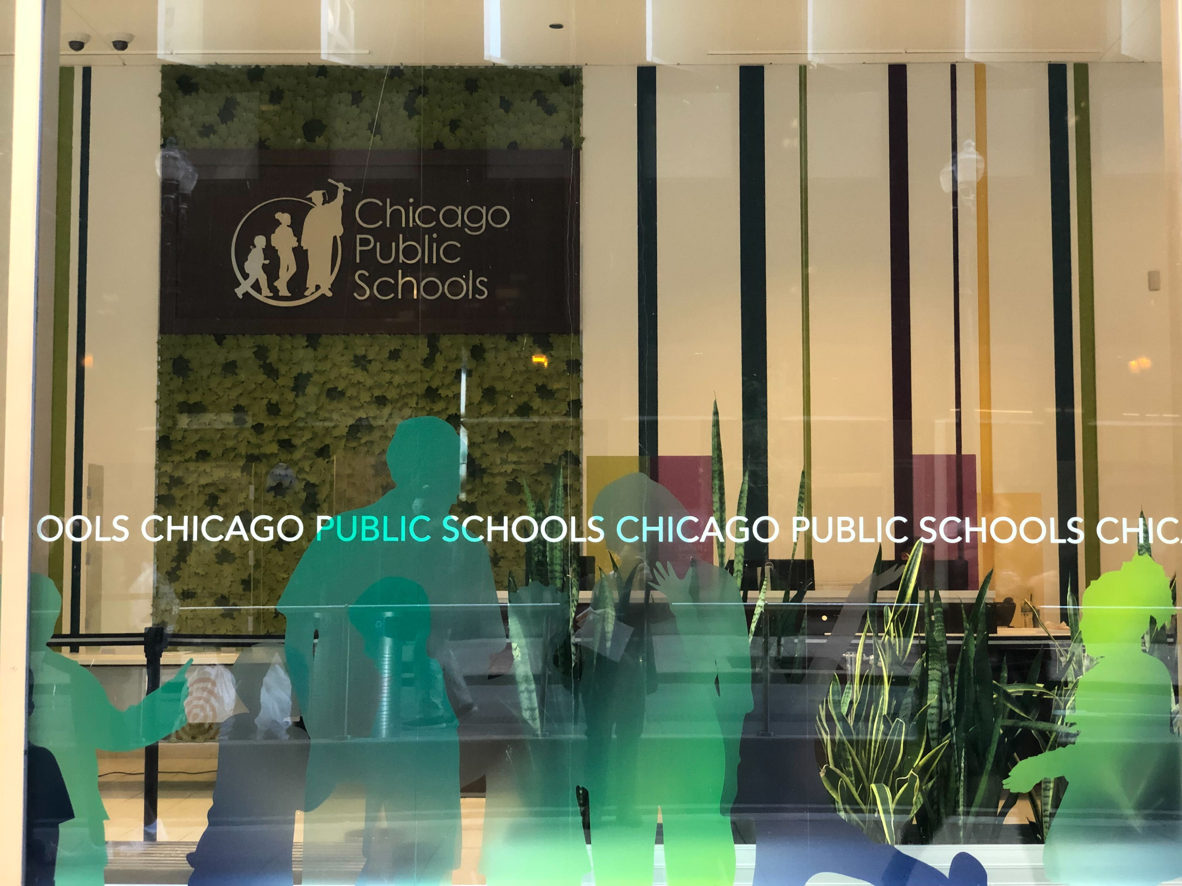 The facade of Chicago Public Schools headquarters, with the district's sign hanging on the wall behind windows with green silhouettes of students.