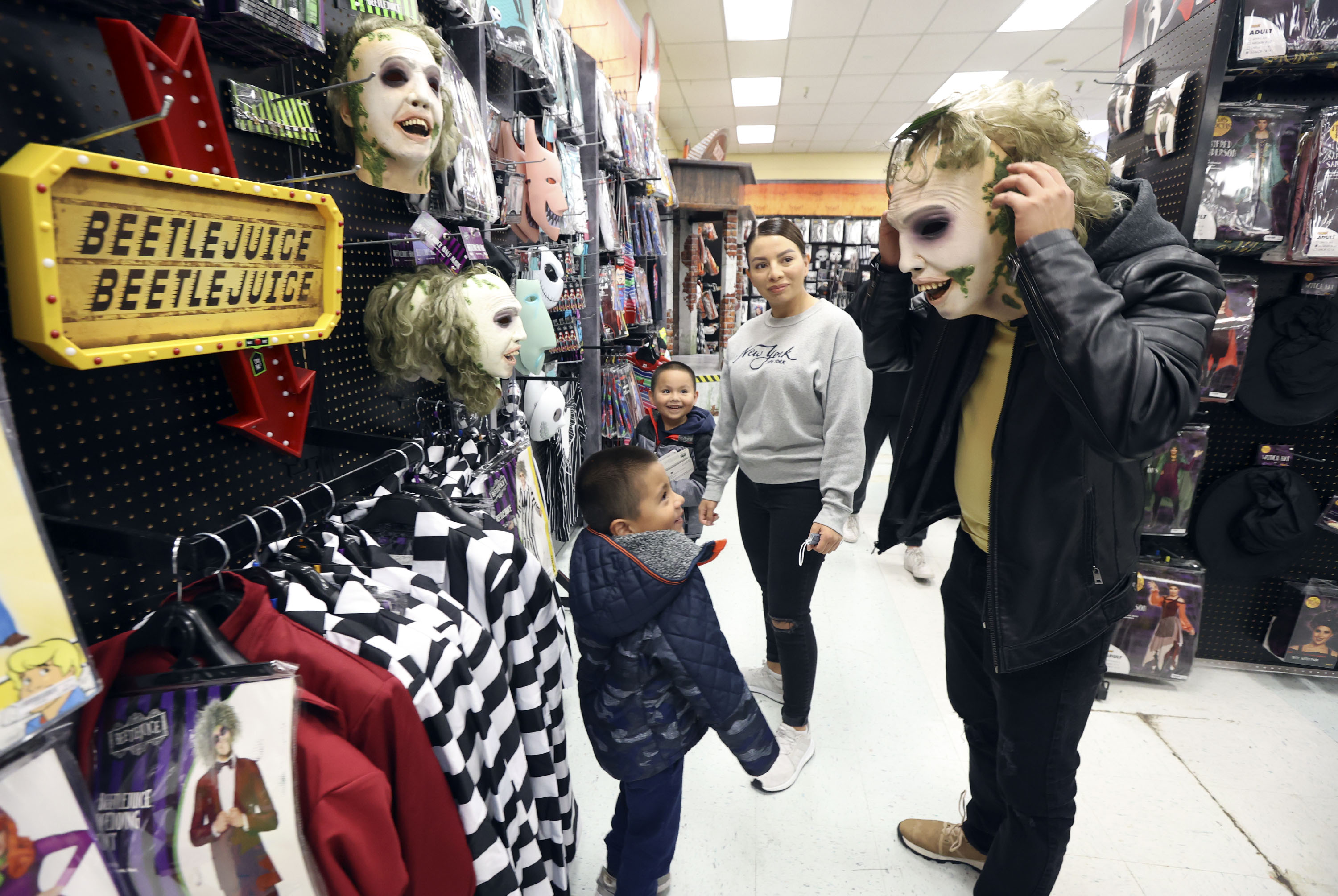 Gustavo Guarneros, left, Dominic Guarneros and Martha Guarneros watch as Alex Aguiniga tries on a Beetlejuice mask while shopping for halloween costumes at Spirit Halloween in Millcreek on Tuesday, Oct. 12, 2021.