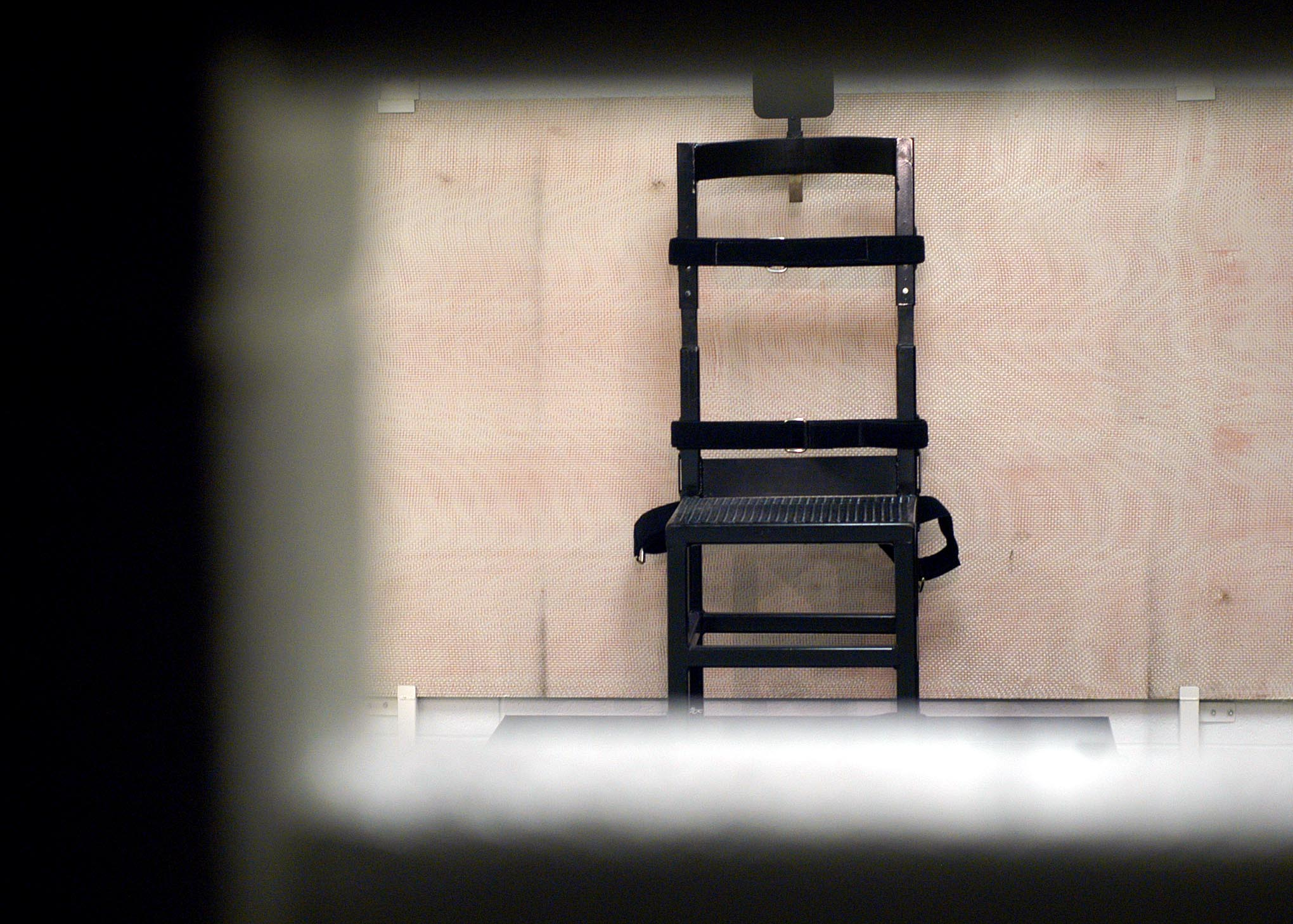 A firing squad chair in the execution chamber at Utah State Prison as seen through the rifle port May 5, 2004.