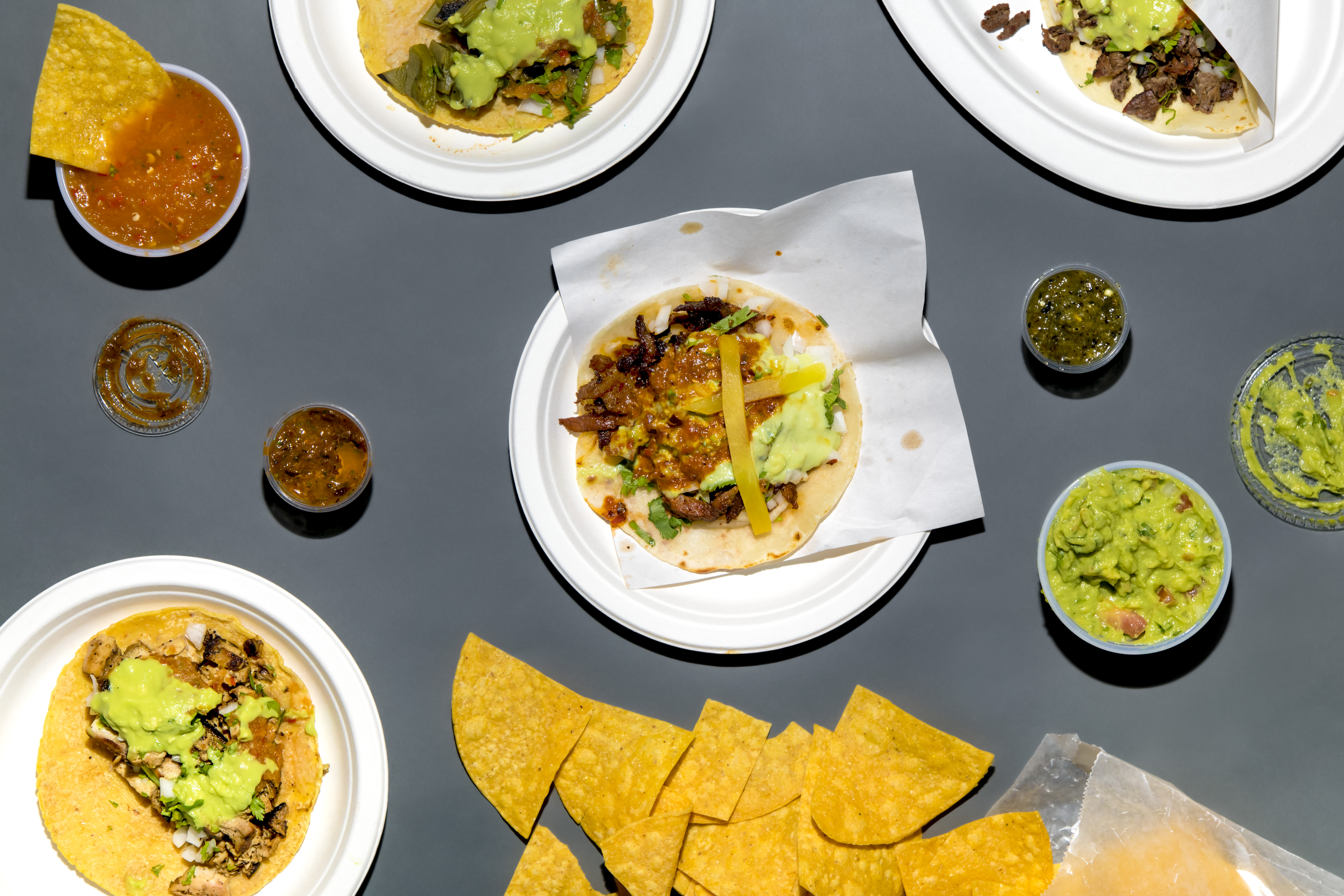An overhead photograph of tacos, chips, guacamole, and plastic sides of salsa.