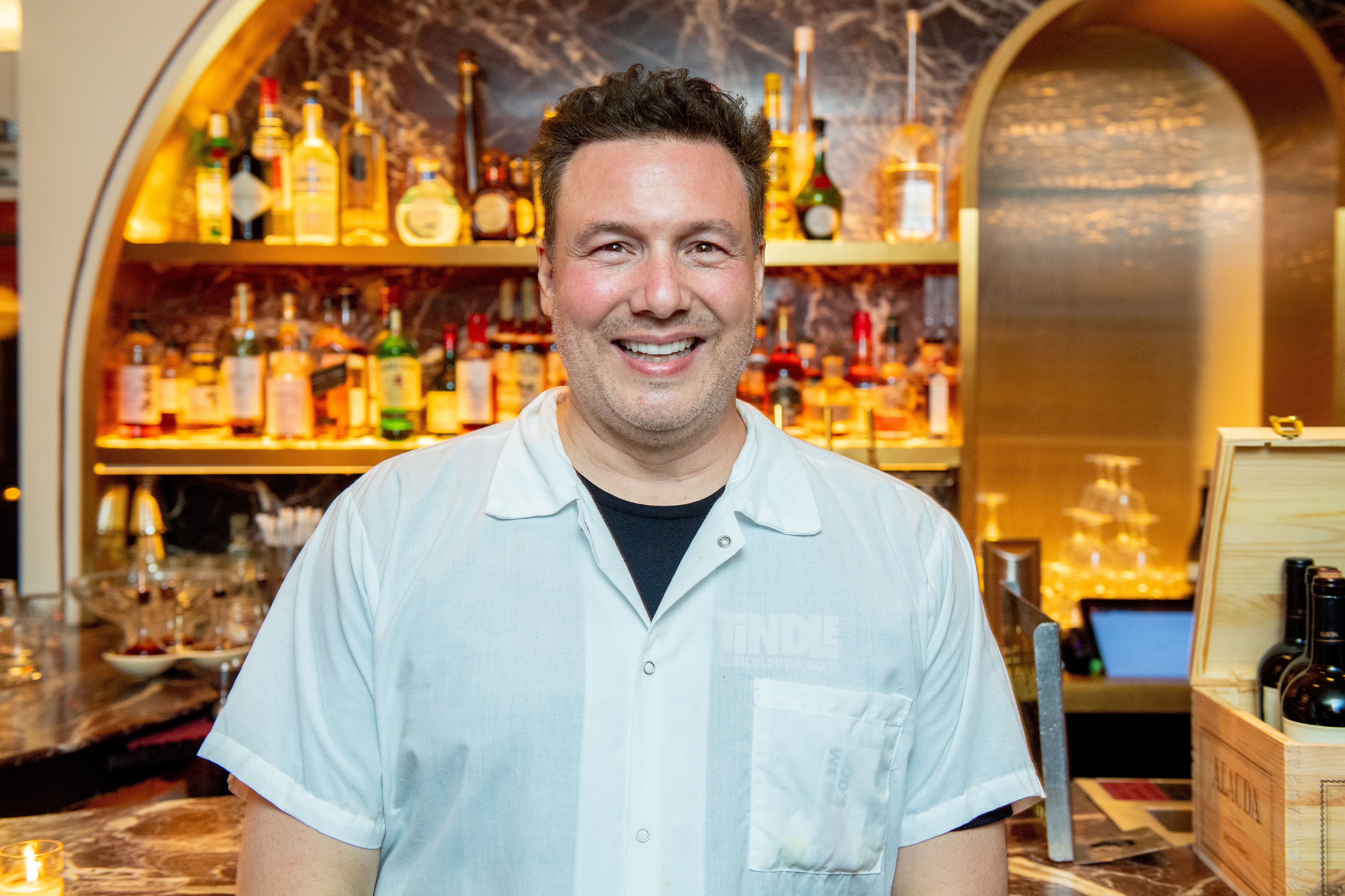 Chef Rocco DiSpirito wearing a white button down shirt over a black tshirt, smiling and standing in front of a bar.