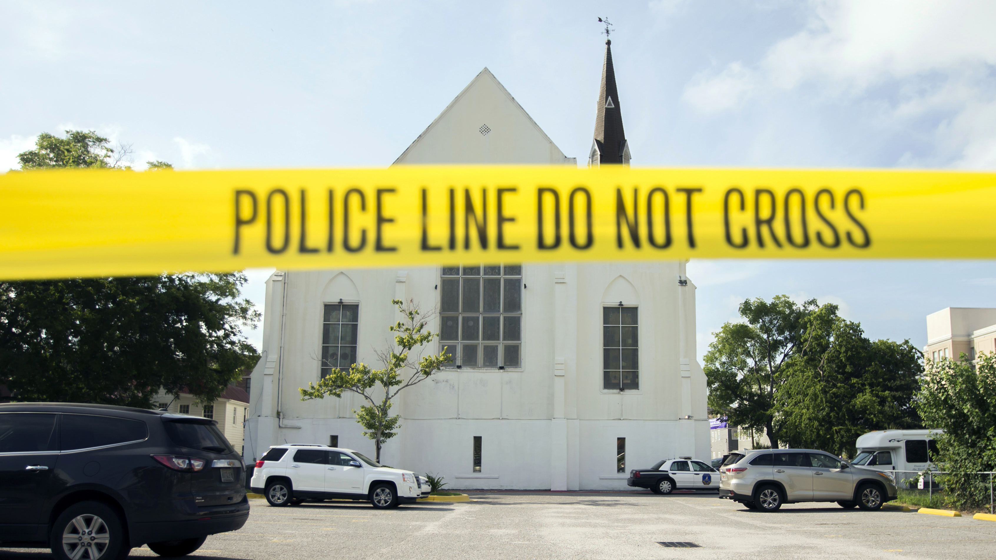 In this June 19, 2015 file photo, police tape surrounds the parking lot behind the AME Emanuel Church as FBI forensic experts work the crime scene, in Charleston, S.C. Families of nine victims killed in a racist attack at a Black South Carolina church have reached a settlement with the Justice Department over a faulty background check that allowed Dylann Roof to purchase the gun he used in the 2015 massacre.