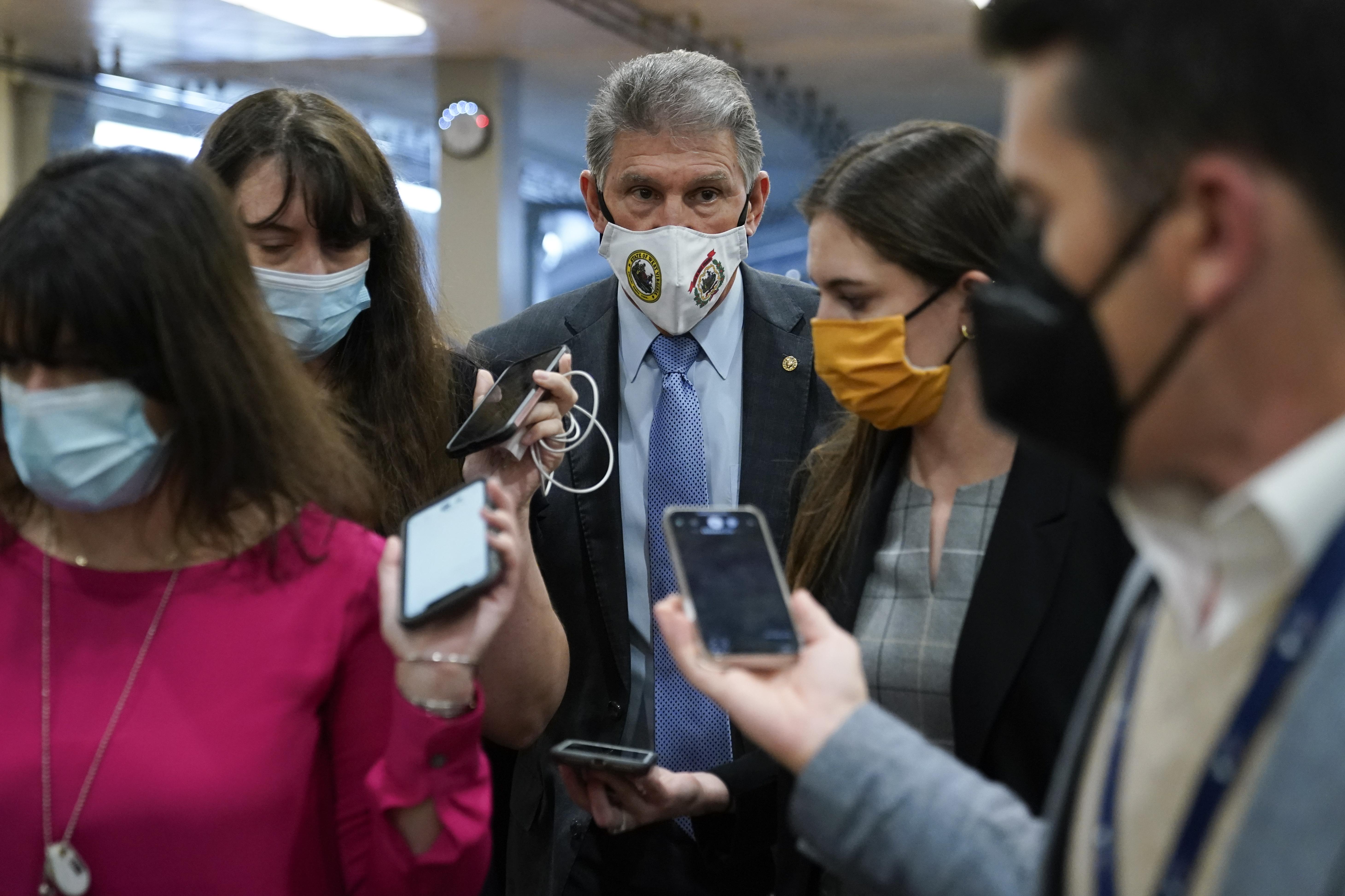 Sen. Joe Manchin, D-W.Va., center, speaks with reporters on Capitol Hill in Washington on Wednesday.