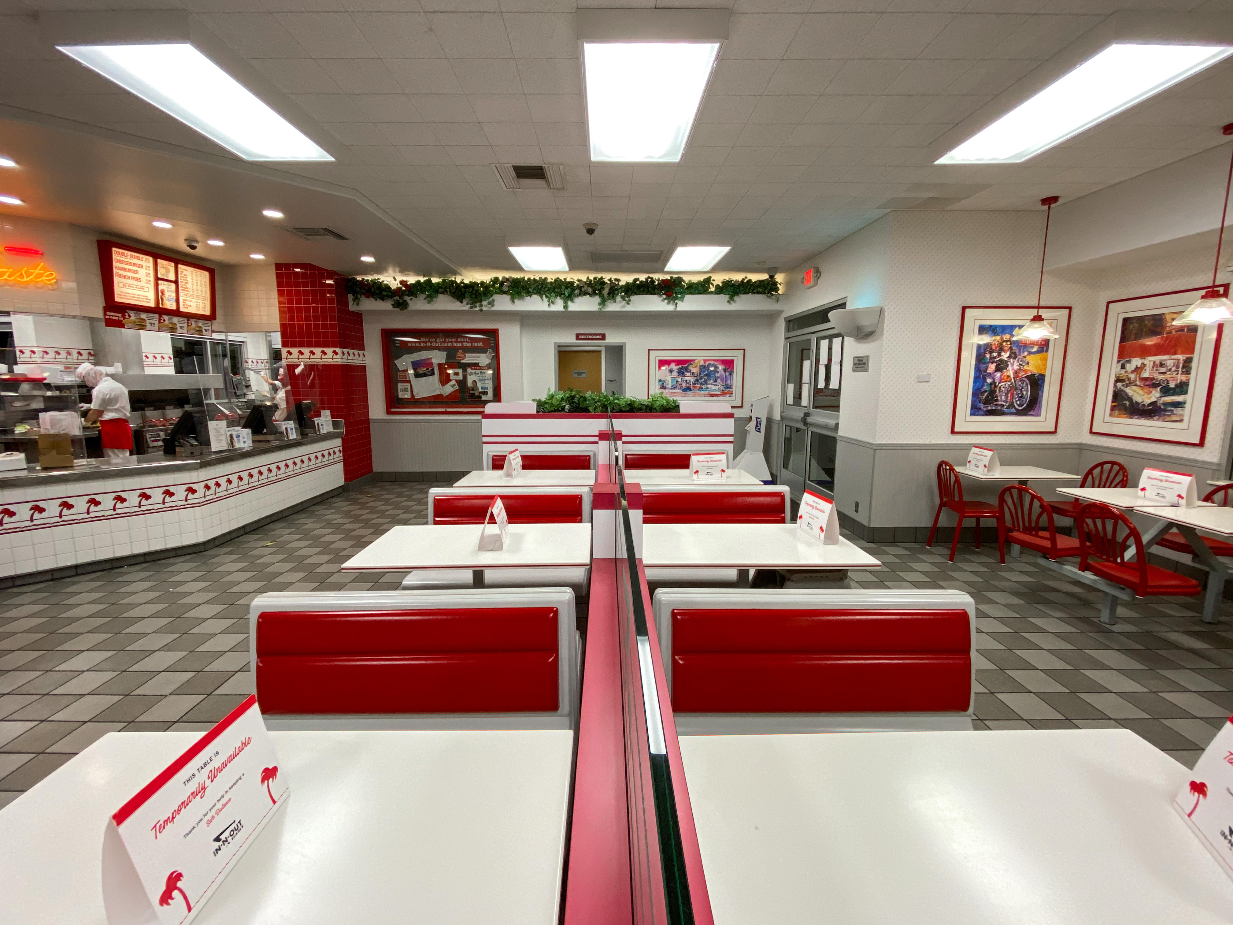 A row of empty booths inside an In-N-Out restaurant
