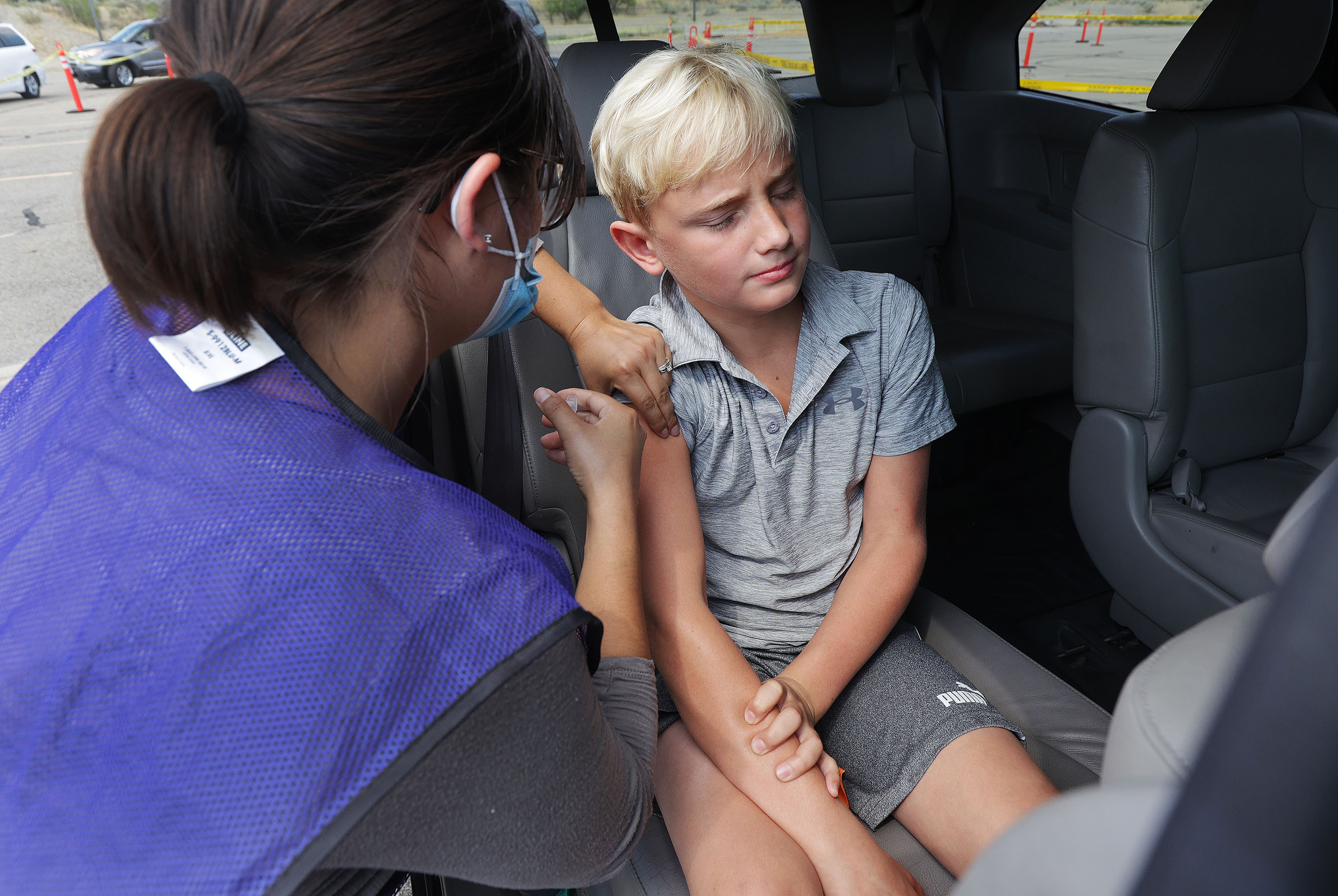 Utah Air National Guard medic Stephanie Young gives Max Lind, 12, a COVID-19 vaccine at Equestrian Park in Highland, Utah.