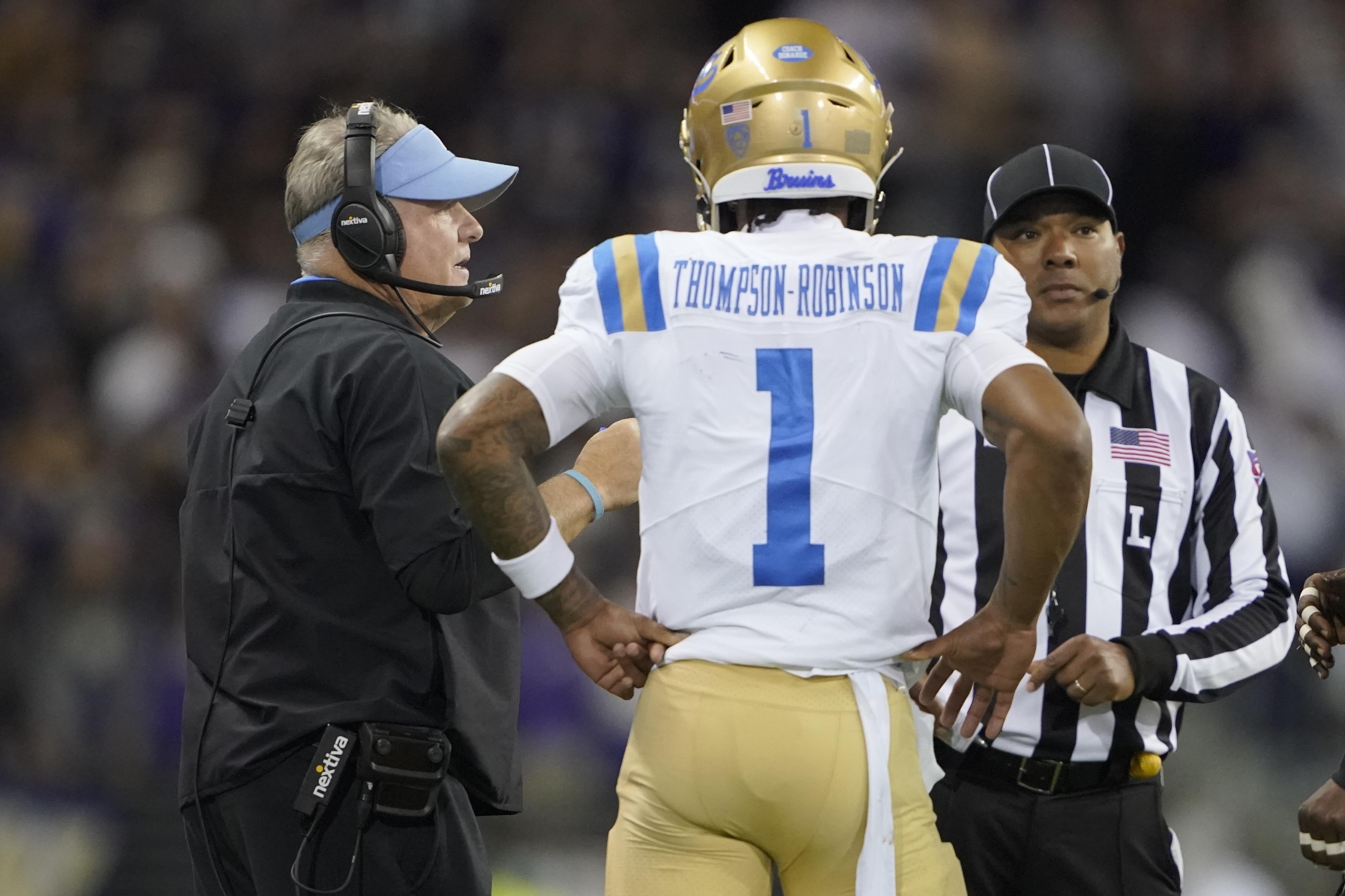 UCLA coach Chip Kelly, left, talks with quarterback Dorian Thompson-Robinson during game against Washington.
