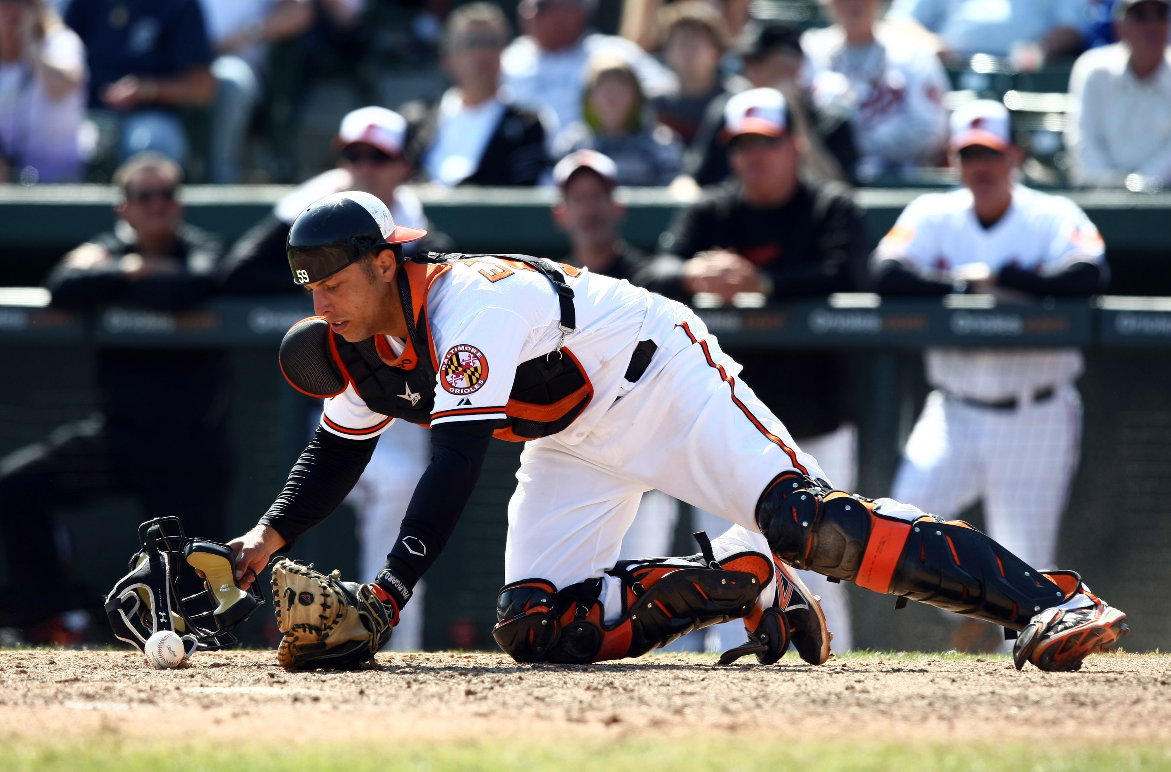 Orioles catcher, Luis Exposito, uses his mask to retrieve a wild pitch.